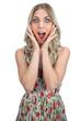 Surprised pretty blonde wearing flowered dress posing