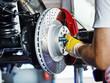 Leinwanddruck Bild - Car mechanic in a garage repairs a bracke