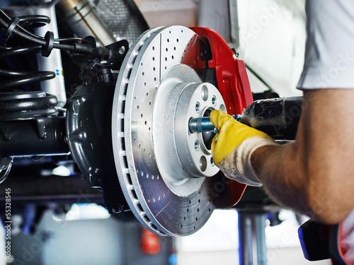 Leinwanddruck Bild Car mechanic in a garage repairs a bracke