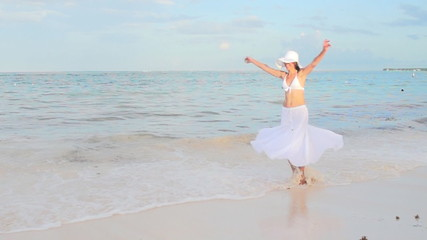 Beautiful woman dancing on the beach.