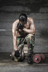 portrait of muscle athlete with camouflage pants weightlifting