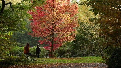 Mum and son sitting on bench in autumn park