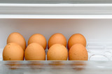 Eggs lying on a regiment in a refrigerator