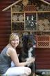 Junge Frau sitzt mit Hund an einem Insektenhotel
