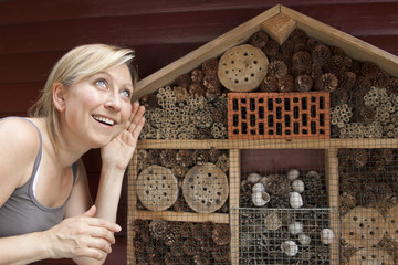 Junge hübsche Frau an einem Insektenhotel