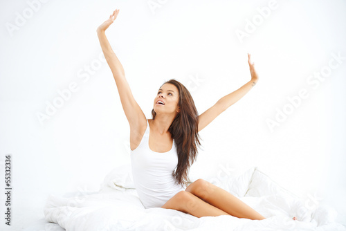 Young lady sitting on the bed and stretching