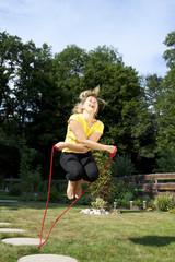 Sportliche Frau springt im Garten Seil