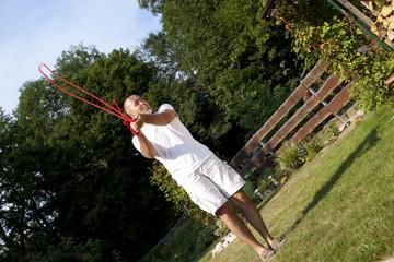 Mann im Garten mit Springseil