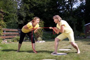 Mutter und Tochter beim Seilziehen im Garten