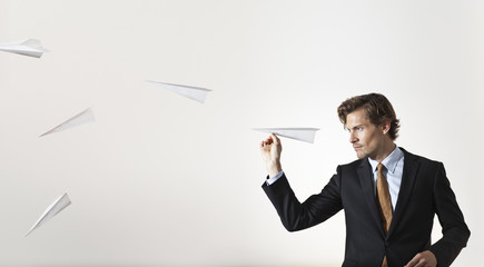 Businessman throwing paper airplanes at target