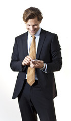 Happy businessman texting and playing with smartphone