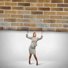 Businesswoman lifting brick wall