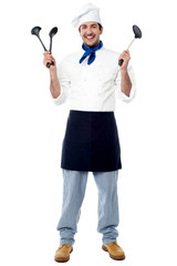 Young chef holding kitchen utensils