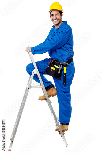 Construction worker climbing up the step ladder