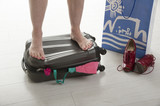 Female standing on suitcase to force shut