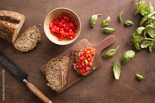 Making bruschetta on wooden table