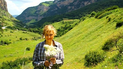 Happy woman with a bouquet of daisies in a meadow