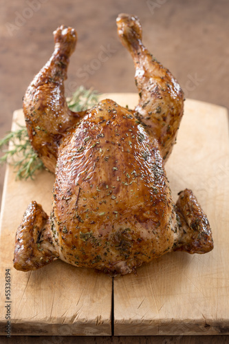 Whole roast chicken on wooden table