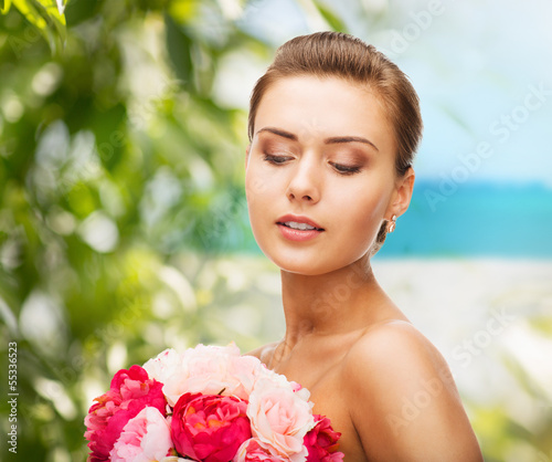 woman wearing earrings and holding flowers