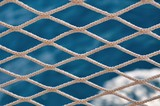 Knitted grid on boat banister with blurred sea on background