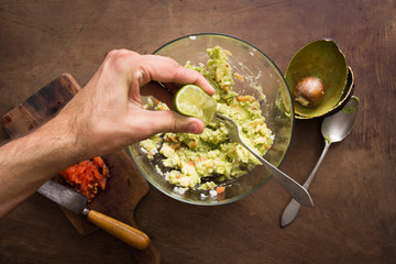 Squeezing lime on guacamole mix