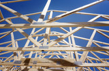 Fototapety New residential construction home framing against a blue sky and