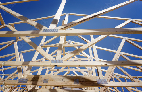New residential construction home framing against a blue sky and