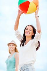 girls playing ball on the beach