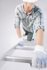 man in helmet and gloves climbing ladder