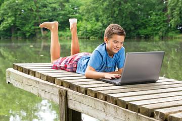 Freundlicher Jugendlicher mit Notebook am idyllischen Teich