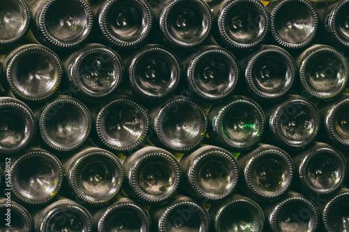 Fototapeta stack of wine bottles in winery - vintage photo