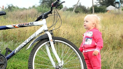 Cute baby try big bicycle.