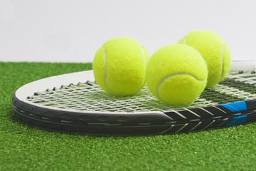 Tennis concept: closeup, tennis racket with balls lies on green