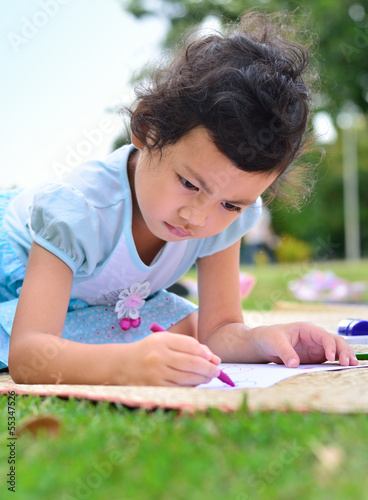 Going back to school,Girl drawing and painting over green grass