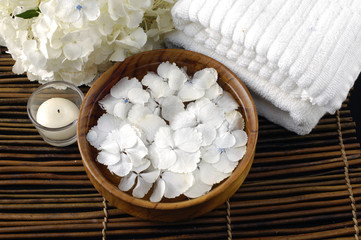 Wooden bowl of white hydrangea and towel on mat