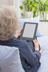 Grauhaarige Frau liest ein Buch auf dem E-Book-Reader