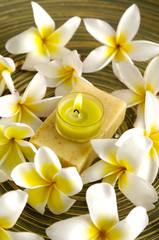 Pile of frangipani and soap with candle in wooden bowl