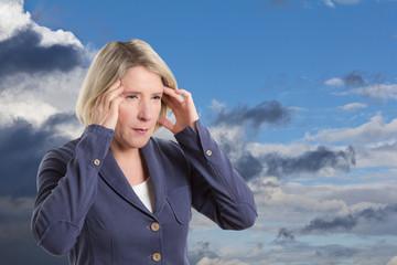 Frau leidet unter Wetterfühligkeit und hat Kopfschmerz