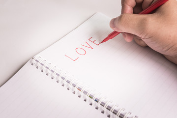 Hand with pen writing a love