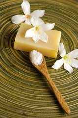 white frangipani flower and stacked soap on wooden plate
