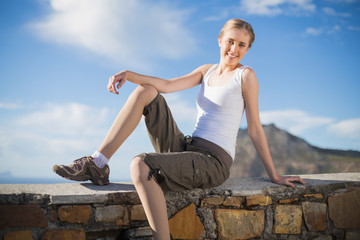 Smiling woman sitting on wall looking at camera