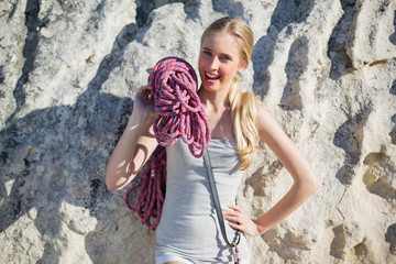 Smiling woman holding climbing equipment leaning at rock