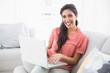 Smiling brunette sitting on her sofa using laptop