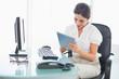 Smiling businesswoman using her digital tablet at desk