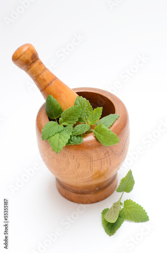 wooden mortar with melissa leaves