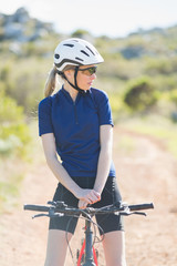 Woman with helmet sitting on bike and looking away