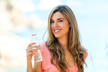 Attractive woman holding water bottle outdoors.