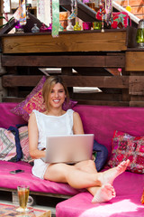 Cute blond relaxing with laptop on couch.
