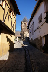 Typical street,steep slope, waterway in the street, church tower