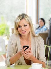 Woman Sending Text Message In Cafe